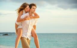 Jeunes couples dans l'amour marchant sur la plage au coucher du soleil Images libres de droits