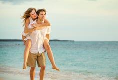 Jeunes couples dans l'amour marchant sur la plage au coucher du soleil Images stock