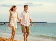 Jeunes couples dans l'amour marchant sur la plage au coucher du soleil Image libre de droits