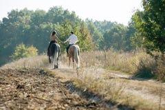 Jeunes couples dans l'amour montant un cheval Image stock