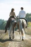 Jeunes couples dans l'amour montant un cheval Photos libres de droits