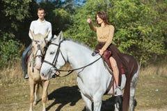 Jeunes couples dans l'amour montant un cheval Photo stock