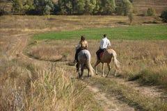 Jeunes couples dans l'amour montant un cheval Photographie stock