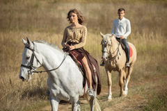 Jeunes couples dans l'amour montant un cheval Photos stock