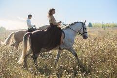 Jeunes couples dans l'amour montant un cheval Image libre de droits