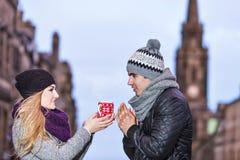 Jeunes couples dans l'amour partageant une tasse de boisson chaude un hiver froid Images stock