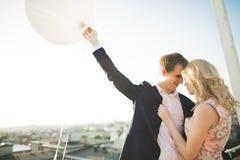 Jeunes couples dans l'amour posant sur le toit avec la vue parfaite de ville tenant des mains et étreindre Beau coucher du soleil Image libre de droits