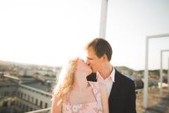 Jeunes couples dans l'amour posant sur le toit avec la vue parfaite de ville tenant des mains et étreindre Beau coucher du soleil Photos libres de droits