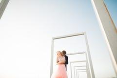 Jeunes couples dans l'amour posant sur le toit avec la vue parfaite de ville tenant des mains et étreindre Beau coucher du soleil Images libres de droits