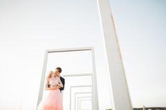 Jeunes couples dans l'amour posant sur le toit avec la vue parfaite de ville tenant des mains et étreindre Beau coucher du soleil Photographie stock libre de droits