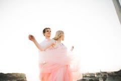 Jeunes couples dans l'amour posant sur le toit avec la vue parfaite de ville tenant des mains et étreindre Beau coucher du soleil Photo libre de droits