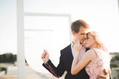Jeunes couples dans l'amour posant sur le toit avec la vue parfaite de ville tenant des mains et étreindre Beau coucher du soleil Photos stock