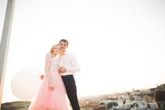 Jeunes couples dans l'amour posant sur le toit avec la vue parfaite de ville tenant des mains et étreindre Beau coucher du soleil Image stock
