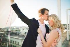 Jeunes couples dans l'amour posant sur le toit avec la vue parfaite de ville tenant des mains et étreindre Beau coucher du soleil Photo stock
