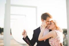 Jeunes couples dans l'amour posant sur le toit avec la vue parfaite de ville tenant des mains et étreindre Beau coucher du soleil Images stock