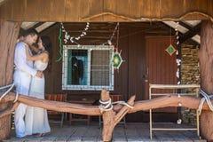 Jeunes couples dans l'amour près de la maison en bois Photos stock