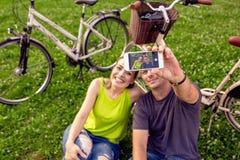 Jeunes couples dans l'amour prenant le selfie en parc image stock