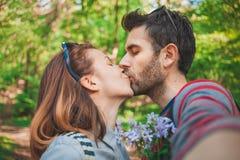 Jeunes couples dans l'amour prenant un selfie tout en embrassant Image stock