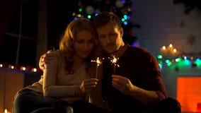 Jeunes couples dans l'amour regardant des lumières de Bengale, faisant le souhait sur Noël, miracle photos libres de droits