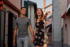 Jeunes couples dans l'amour regardant la fenêtre de magasin dans une allée dans l'ascona pendant le coucher du soleil image stock