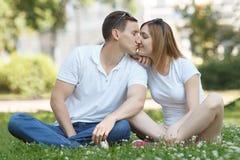 Jeunes couples dans l'amour s'embrassant dehors en parc Photographie stock libre de droits