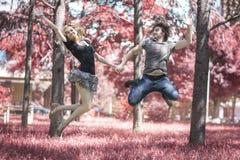 Jeunes couples dans l'amour sautant dans le ciel dans la forêt rouge Photographie stock