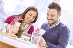 Jeunes couples dans l'amour se reposant dans un café et une communication Images stock