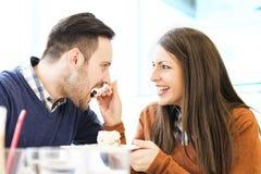 Jeunes couples dans l'amour se reposant dans un café, mangeant le gâteau Photos libres de droits