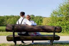 Jeunes couples dans l'amour se reposant ensemble sur un banc en parc Photos stock