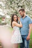 Jeunes couples dans l'amour se reposant dans le jardin de floraison arbres de floraison de blanc photographie stock libre de droits