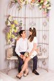 Jeunes couples dans l'amour se reposant sur l'embrassement de sofa Image stock