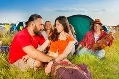 Jeunes couples dans l'amour se reposant sur l'herbe au terrain de camping Image stock