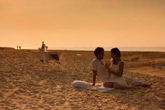 jeunes couples dans l'amour se reposant sur la plage Photo libre de droits