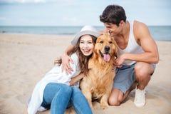 Jeunes couples dans l'amour se reposant sur la plage avec le chien Photo stock