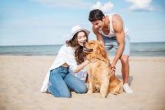 Jeunes couples dans l'amour se reposant sur la plage avec le chien Photographie stock