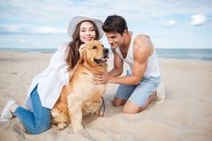 Jeunes couples dans l'amour se reposant sur la plage avec le chien Photos stock