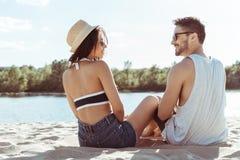 Jeunes couples dans l'amour se reposant sur la plage tout en passant le temps ensemble Image stock