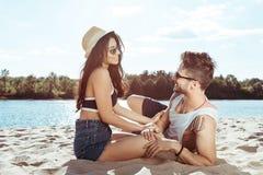 Jeunes couples dans l'amour se reposant sur la plage tout en passant le temps ensemble Photographie stock