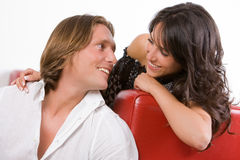 Jeunes couples dans l'amour se reposant sur le sofa Images stock