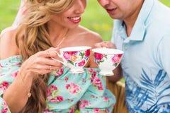 Jeunes couples dans l'amour se reposant sur un plaid de pique-nique en parc, thé potable et appréciant leur jour en nature Image stock