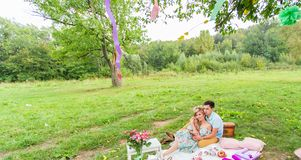 Jeunes couples dans l'amour se reposant sur un plaid de pique-nique en parc, thé potable et appréciant leur jour en nature Images libres de droits