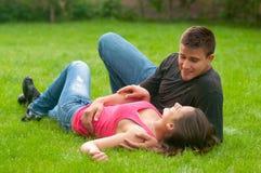 Jeunes couples dans l'amour se situant dans l'herbe Photographie stock libre de droits