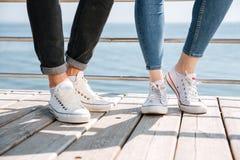 Jeunes couples dans l'amour se tenant dans des chaussures en caoutchouc Photo libre de droits