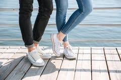 Jeunes couples dans l'amour se tenant dans des chaussures en caoutchouc Image stock