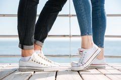 Jeunes couples dans l'amour se tenant dans des chaussures en caoutchouc dehors Photo stock
