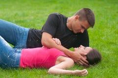 Jeunes couples dans l'amour se trouvant sur l'herbe Photographie stock