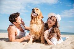 Jeunes couples dans l'amour se trouvant sur la plage avec le chien Photo libre de droits