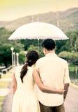 Jeunes couples dans l'amour sous un parapluie après pluie Image stock