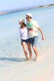 Jeunes couples dans l'amour sur des holdays marchant en eau de mer Images libres de droits