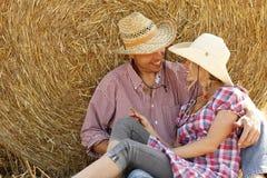 Jeunes couples dans l'amour sur des meules de foin Photos libres de droits